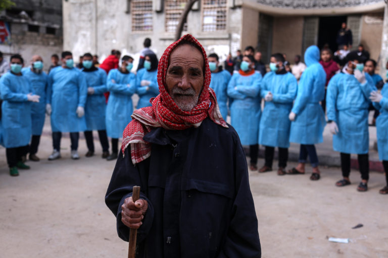 Man stands in front of a group of Palestinian workers waiting to sterilize buildings in the Gaza Strip, March 24, 2020.