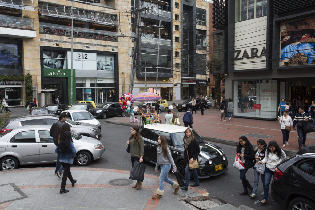 A busy intersection in Bogota. The street is flanked by shoppingmalls. The store Zara is on the ground floor. There are cars parked by